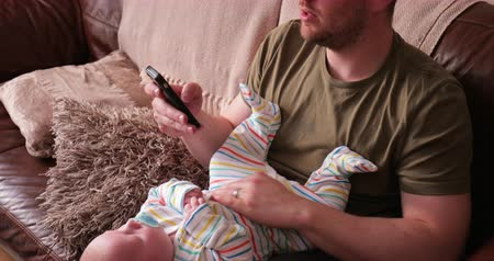 emzik : Father resting baby boy on his lap while he sleeps and holds his phone in his other hand. Stok Video