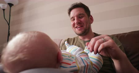 kalmak : Close-up of babies head while he lies on his dads lap. His dad is rubbing his belly with one hand and going through his phone with his other hand. Stok Video