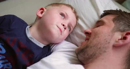 рекреационных преследования : Little boy cuddling up with his dad in bed. There talking about something interesting before they go to sleep. Стоковые видеозаписи