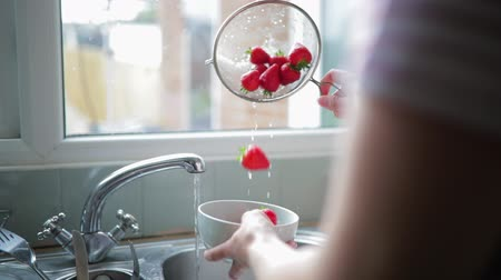 over the shoulder view : Woman rinsing some strawberries under the water in the kitchen so that theyre good enough to eat for after their dinner.