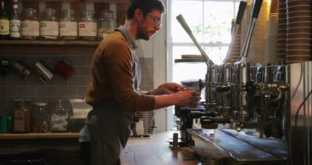 jarro : Male barista filling up the coffee milk pitcher with hot milk from the coffee machine.