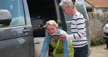 modo : Two women sorting out their food delivery for the restaurant they both work in.