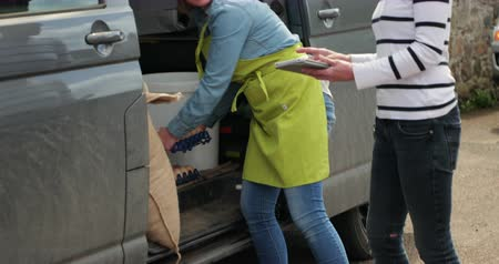 representante : Two women sorting out their food delivery for the restaurant they both work in.