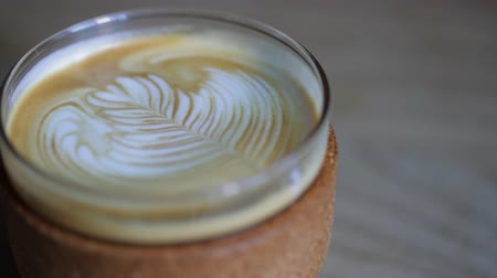 латте : Panning shot of a glass of latte sat on a table.