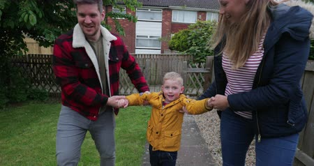 front or back yard : Mum and dad swinging their little boy high up in the air while they walk through their garden after being out on a little walk. Stock Footage