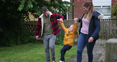 front or back yard : Mum and dad swinging their little boy in the air by his arms while walking through their garden after being out shopping for groceries.