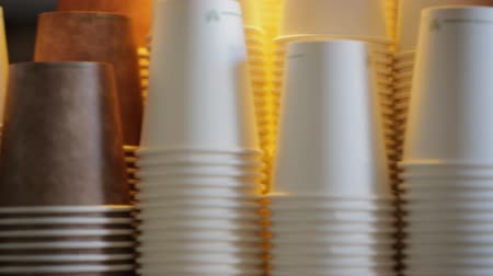 lids : Panning shot of paper coffee cups stacked up on each other.