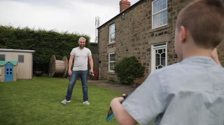 front or back yard : Little boy and his father standning outdoors in a back garden. Theya re playing catch with a tennis ball and velcro mitts. Stock Footage