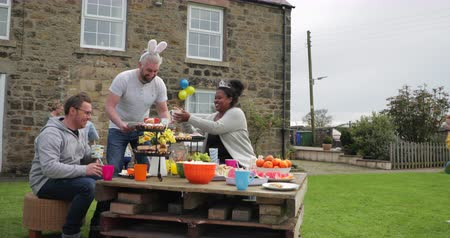 easter : Mid adult man laughing and having fun with other parents at a garden party. He is wearing rabbit ears and holding a chocolate easter egg while smiling.