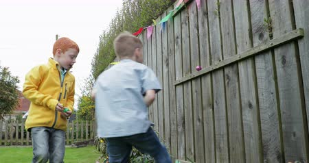 front or back yard : Slow motion shot of two little boys finding chocolate easter eggs which have been hidden in a back garden. Stock Footage