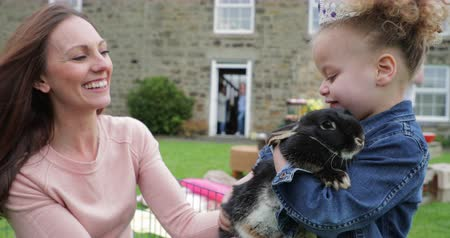 temas animais : Little girl excited while stroking a pet rabbit ourdoors at a easter garden party.