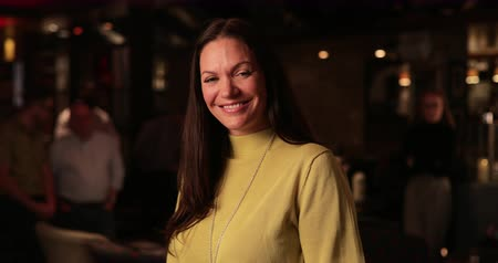 focus on foreground : Video portrait of a mature adult woman looking at the camera and smiling.
