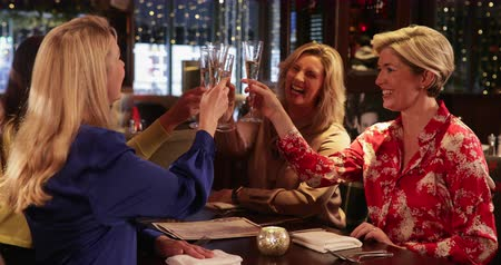 champagne flute : Four female friends sitting and relaxing in a restaurant, they are enjoying themselves and laughing. They are making a celebratory toast. Stock Footage
