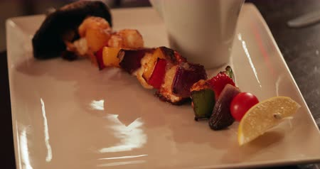 establishment : Panning shot of a vegetarian skewer which has been presented on a plate with gravy on a wooden table in a restaurant.