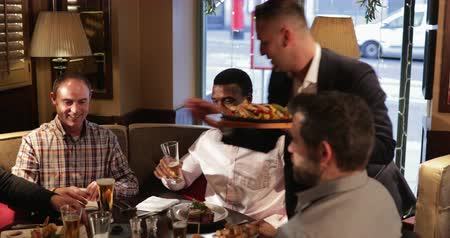 establishment : Panning shot of a male waiter carrying food over to a table of male friends. They are excited for the food to arrive.