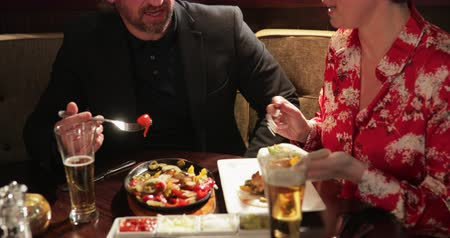 milestone : Panning shot of a mature couple on a date in a restaurant. They are talking and sharing a dish of chicken fajitas.