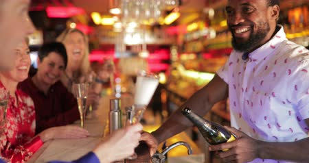 etnia africano : Panning shot of a mid adult bartender pouring a glass of champagne at the bar counter for a mature woman who is sitting with a small group of friends. Stock Footage