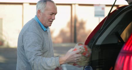 modern manhood : Senior man is filling his car boot with shopping bags.