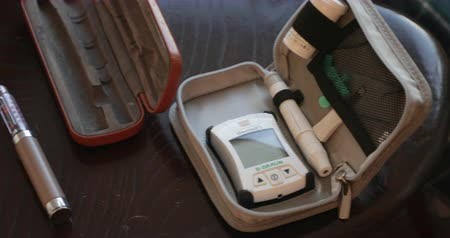 mérés : Overhead panning shot of a blood glucose testing kit on a coffee table.