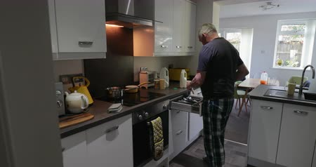 one man only : Senior man is making instant porridge in the kitchen of his home.