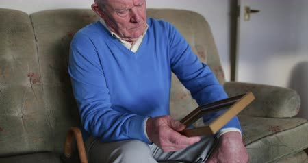 luto : Senior man is sitting alone in the living room of his home, looking at an old photo. Stock Footage