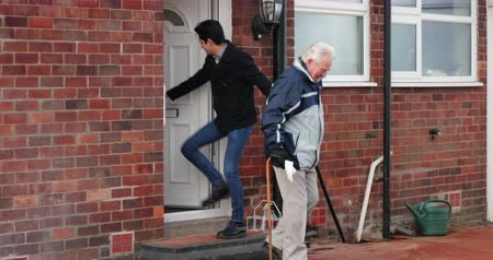 front or back yard : Teenage boy is helping his grandfather out of the door and down the steps of his house.