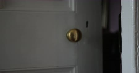 image house : Close-up of a old fashioned door and door handle in a house. The door is opened and an unrecognisable person walks through the door and lets it close. Stock Footage