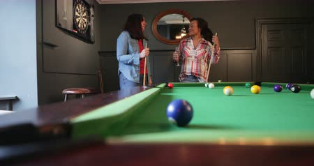 biljart : Two female adults talking and enjoying a drink while playing a game of eight ball pool.