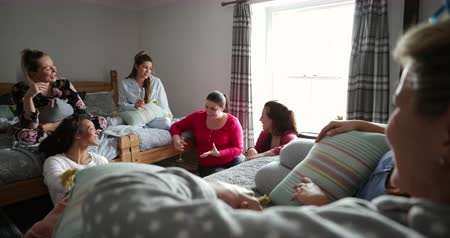 champagne flute : Small group of female friends relaxing and talking while enjoying a girls night in. They are sitting in a bedroom in their pyjamas.