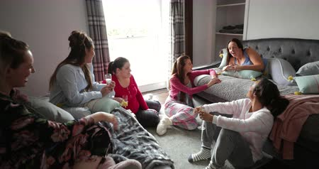 champagne flute : Small group of female adults relaxing and having fun while relaxing in their pyjamas.