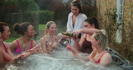 tüm : Small group of female friends socialising and relaxing in the hot tub on a weekend away. They are celebrating with a glass of champagne. Stok Video