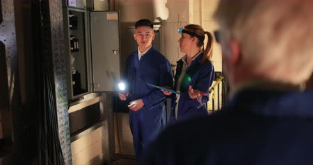 Trainee Electricians Using a Switch Board