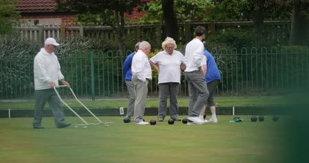 A front-view shot of a small group of senior friends at a bowling green.