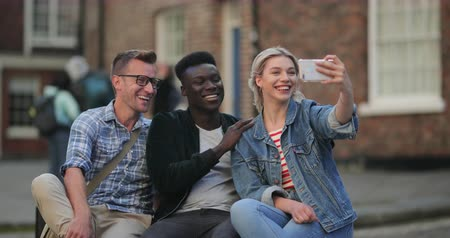 A woman taking a selfie and laughing with two other men while sitting down on a bench.