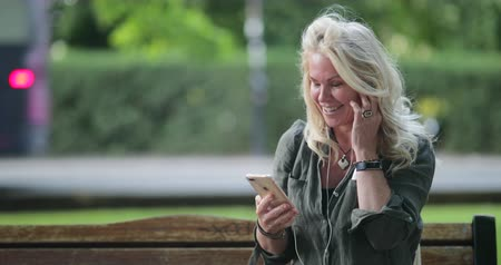 A woman sitting on a park bench using headphones to listen and talk to someone on her mobile phone. She is smiling and laughing.