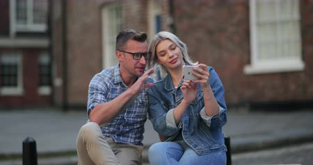 A woman showing a man something on her mobile phone while sitting on a bench.