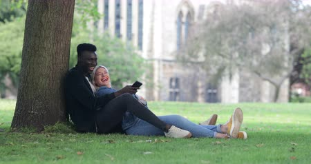 A man and woman sitting in a park against a tree. The woman is sitting in between the mans legs while he shows her something on his mobile phone. The woman is looking up at the man and laughing.