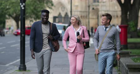 A businesswoman is walking with two businessmen to work through the city.