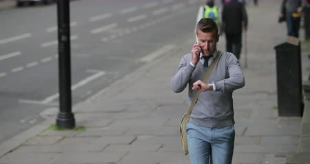 move well : Businessman on his way to work while talking on the phone and checking the time.