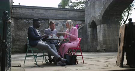 Two businessmen and a businesswoman sitting at an outdoor table in a city having a hot drink while discussing work on a digital tablet.