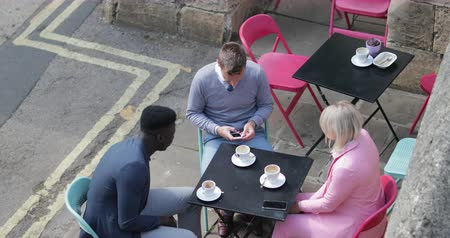 Two businessmen and a businesswoman sitting at an outdoor table in a city having a hot drink while discussing work and looking at mobile phones. 動画素材