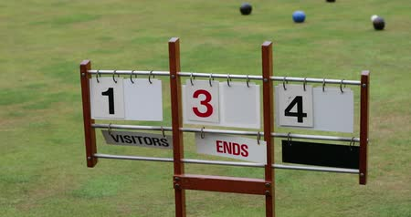 A close-up shot of a lawn bowling scoreboard on grass, showing double digits. 動画素材