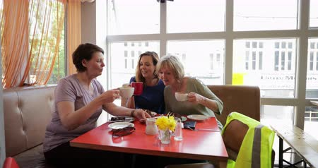 kahve molası : A small group of mature female friends sitting and talking in a cafe, having a toast.