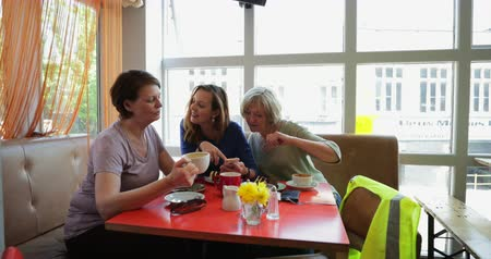 тост : A small group of mature female friends sitting and talking in a cafe, pointing at a phone.