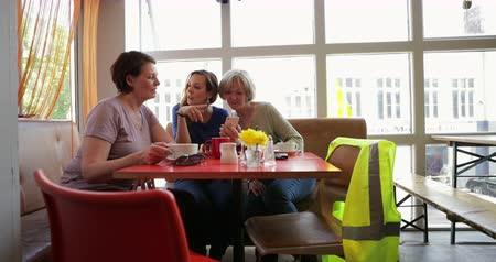 kahve molası : A small group of mature female friends sitting and talking in a cafe, pointing and laughing at a phone.