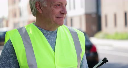 A side view shot of a mature man wearing a high visibility jacket. He is ready to clean the environment.