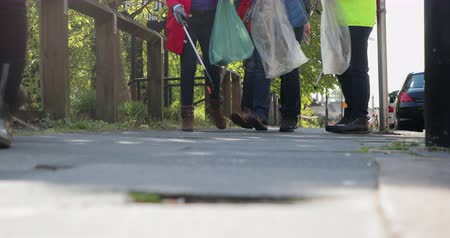 A low angle front view shot of a group of people walking. They are carrying picking up sticks and plastic bags.