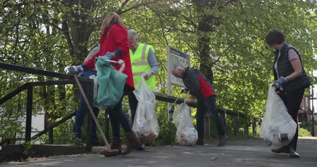 A group of five mature adults cleaning up the streets by picking up litter.