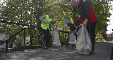 sustainable resources : A group of five mature adults picking up litter off the ground outdoors.