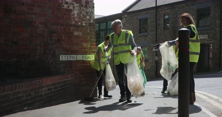 A group of five mature adults clearing up the streets as they pick up litter.
